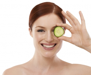 Cropped shot of a beautiful young woman holding a slice of cucumber against a white background